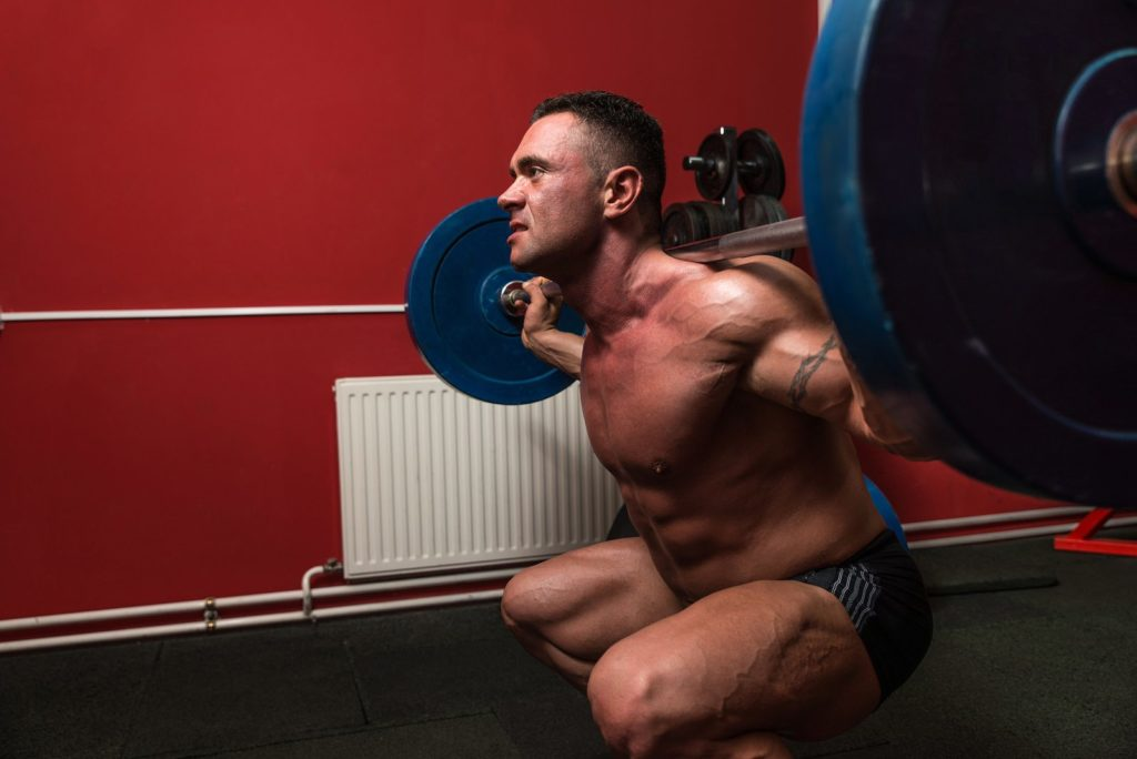 Athlete crouches with a barbell
