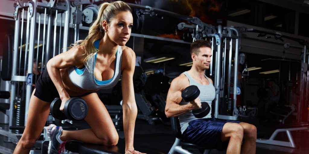 The girl and the guy in the gym perform exercises